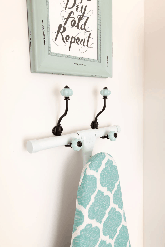 Laundry room organization hack. Simply hang ironing board to two decorative hooks!
